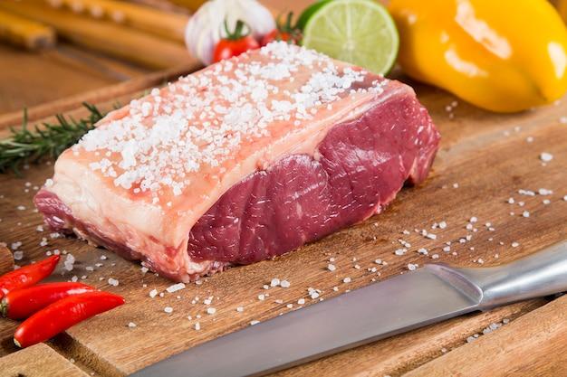Seleção de carne crua na tábua de madeira.
