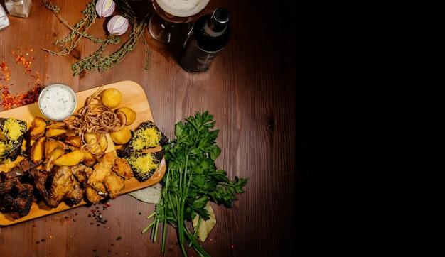 Seleção de cerveja e lanches. batatas fritas, peixe, salsichas de cerveja em cima da mesa. vista do topo