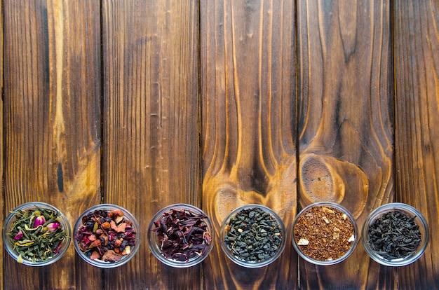 Seleção de chás variados em tigelinhas transparentes sobre fundo de madeira natural