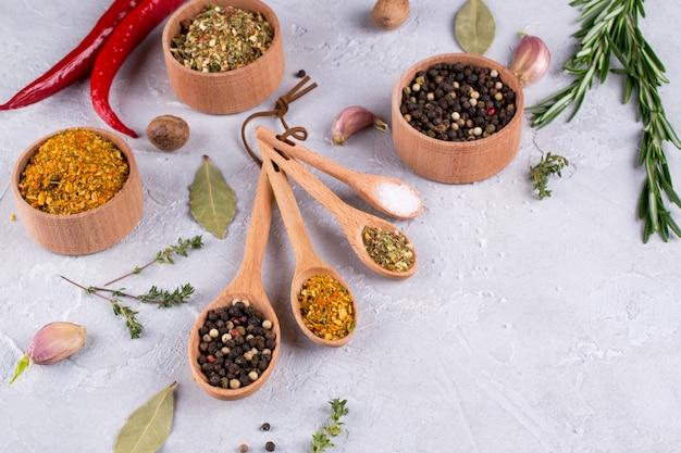 Seleção de ervas e especiarias em colheres de madeira - alecrim, alho, sal, pimenta na mesa cinza. comida plana leigos. fundo de culinária de alimentos