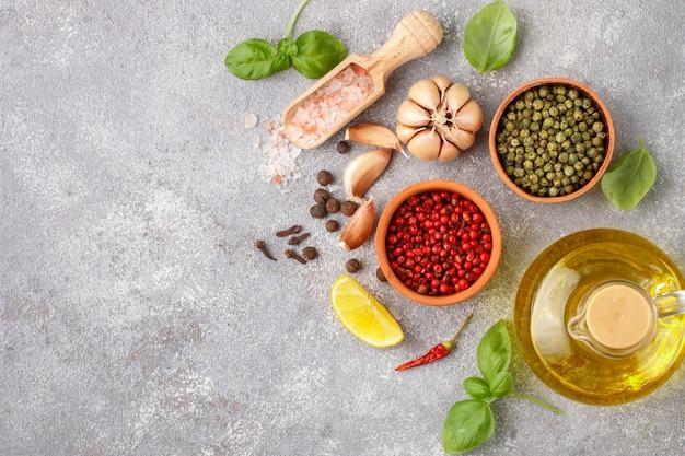 Seleção de especiarias e ervas - alho, sal, pimenta rosa, verde e preta, limão, manjericão, azeite, ingredientes para cozinhar, fundo de alimentos na lousa cinza, vista superior
