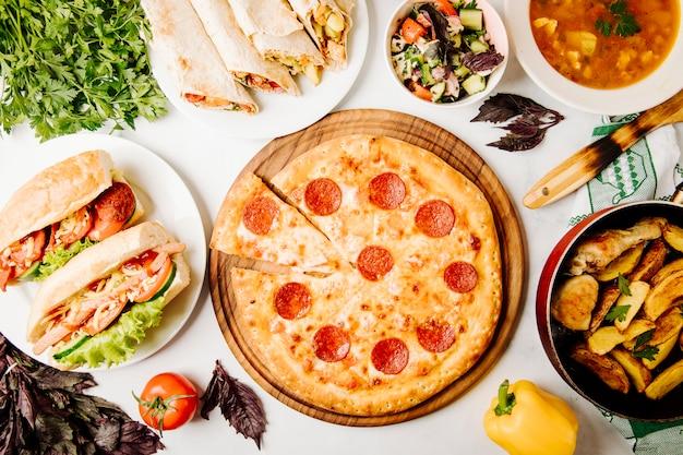 Seleção de fast food, incluindo pizza, sanduíches, shaurma, salada, batatas grelhadas e sopa.