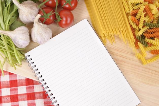 Seleção de macarrão com livro de receitas em branco