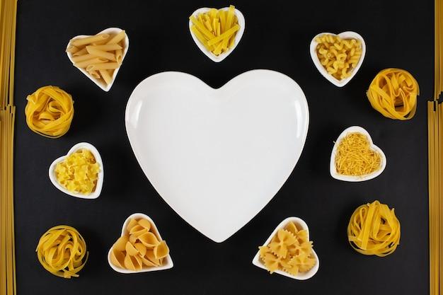 Seleção de massas alimentícias em pratos de porcelana em formato de coração