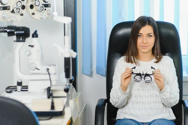 Seleção de óculos para visão para a mulher. salão ótico. óptico. lentes de teste.