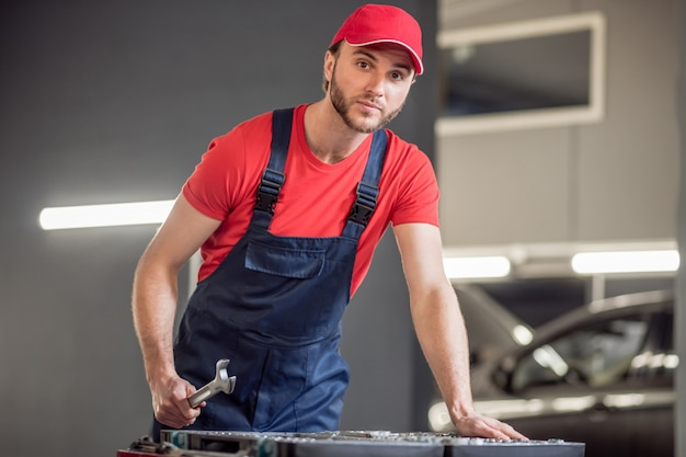 Seleção de peças. jovem atraente barbudo com boné vermelho e chave inglesa perto da caixa com peças em oficina mecânica