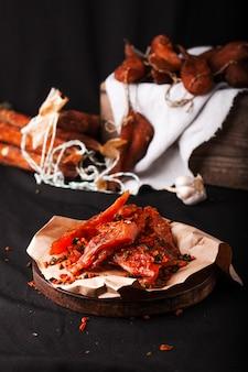 Seleção de salsichas de carnes defumadas decoradas com alho e pimenta. salsicha de carne de porco curada seca espanhola. carne em um prato durante o churrasco. salsicha, peito.