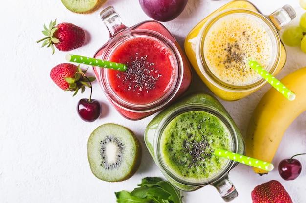 Seleção de smoothies de frutas multicoloridas em frascos de vidro.