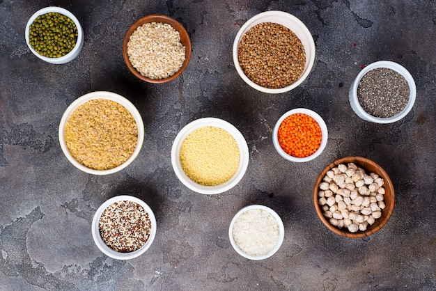 Seleção de superalimentos e cereais em taças em fundo cinza de concreto