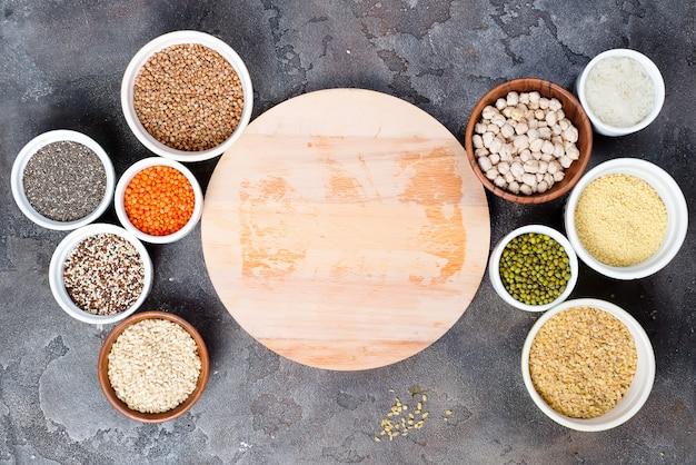 Seleção de superalimentos e cereais em tigelas com placa de madeira para o seu texto