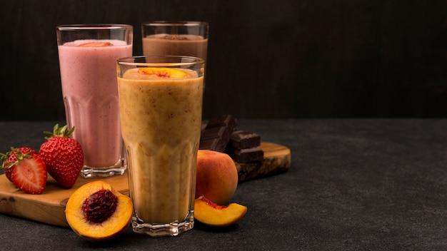 Seleção de três copos de milkshake com chocolate e frutas