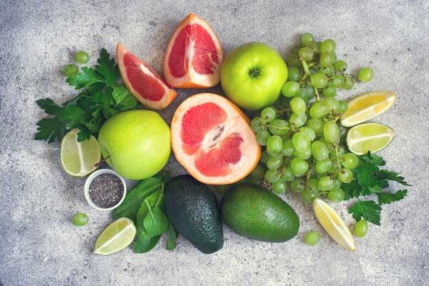 Seleção de vegetais verdes e frutas em um concreto cinza de volta