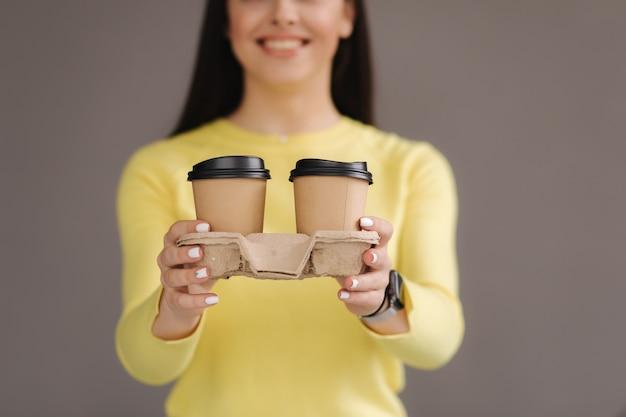 Seleção do meio de mulher morena em moletom amarelo segurar duas xícaras de cappuccino em fundo cinza no estúdio. concentre-se em copos.