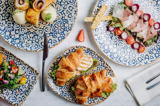Seleção mista de lanches e sanduíches em pratos decorativos.