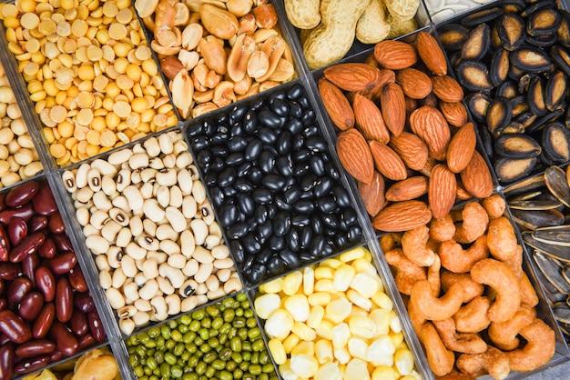 Selecione diferentes grãos integrais feijões e legumes sementes lentilhas e nozes lanche colorido fundo vista superior - colagem vários feijões misturam ervilhas agricultura de alimentos saudáveis naturais para cozinhar ingredientes