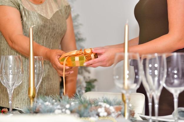 Selecione o foco de uma mulher dando uma caixa de presente embrulhada para outra em uma mesa fora de foco
