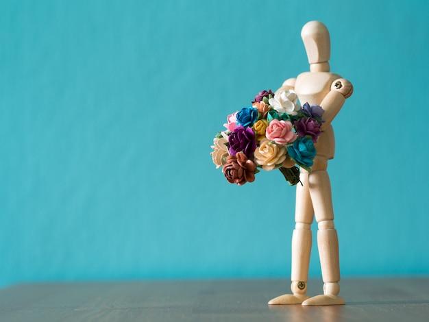 Selecione o foco do boneco de madeira. o boneco de madeira mantém flor e em pé sobre a mesa de madeira.