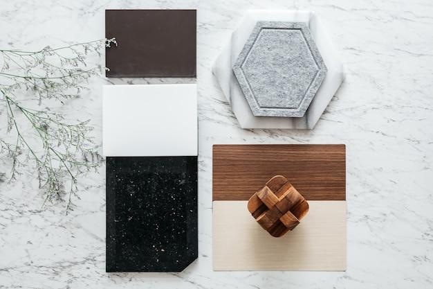 Seleções de materiais, incluindo ladrilho de granito, ladrilho de mármore, ladrilho acústico, laminado de madeira de nogueira e cinza com planta na mesa de tampo de mármore.
