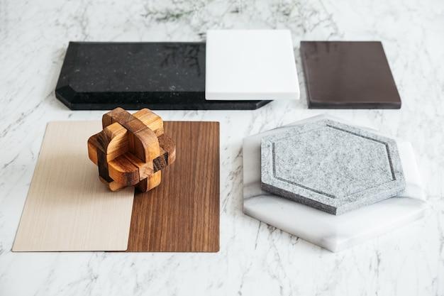Seleções de materiais, incluindo ladrilho de granito, ladrilho de mármore, ladrilho acústico, laminado de madeira de nogueira e cinza com plantas e flores na mesa superior de mármore.