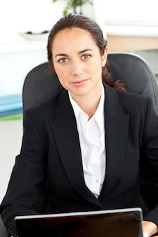 Selfassured empresária sentado em sua mesa na frente de seu laptop