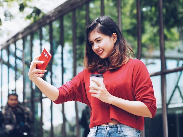 Selfie asiático da mulher ela mesma e copo de café da terra arrendada à disposição.