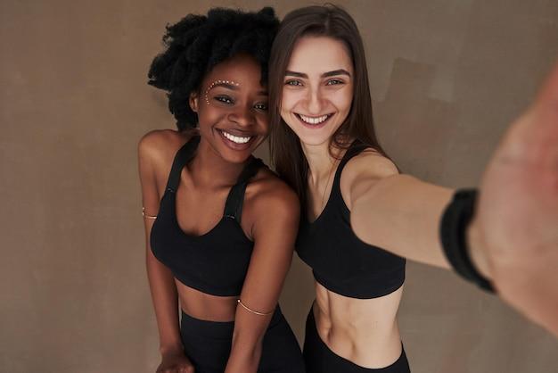 Selfie chegando. duas amigas multiétnicas carrinhos