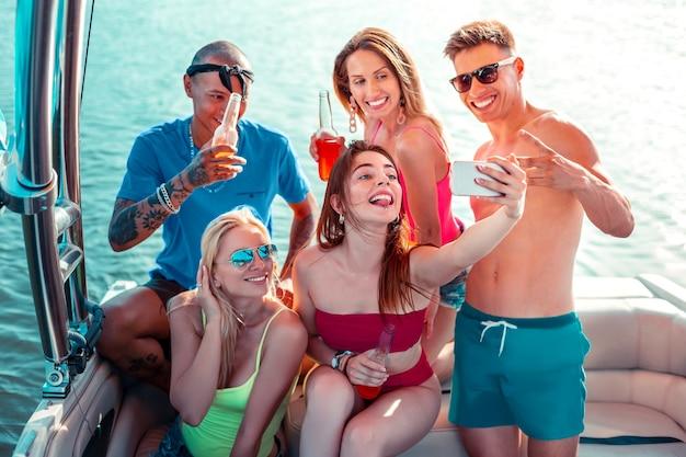 Selfie com amigos. feliz garota de cabelos compridos sentada em um barco de recreio enquanto tira uma selfie com seus amigos sorridentes fazendo caretas