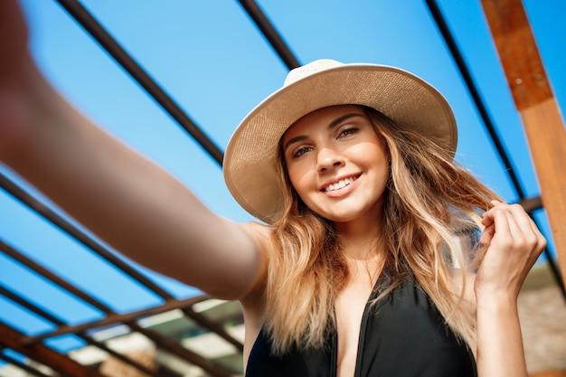 Selfie da bela jovem alegre de chapéu repousa na praia de manhã