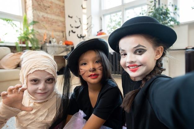 Selfie de alunos positivos com maquiagem de halloween posando juntos em uma sala decorada