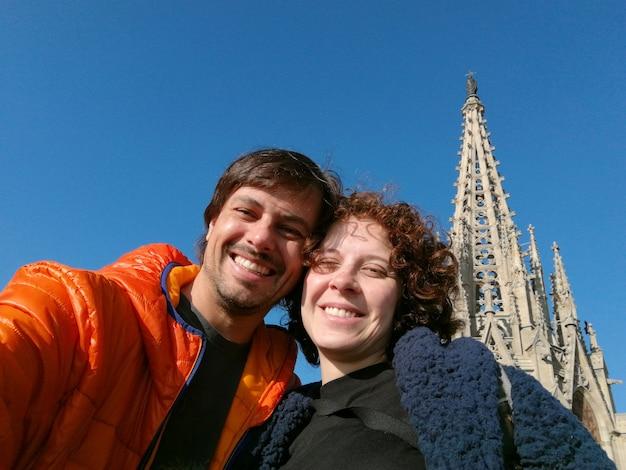 Selfie de casal com a catedral de barcelona ao fundo.