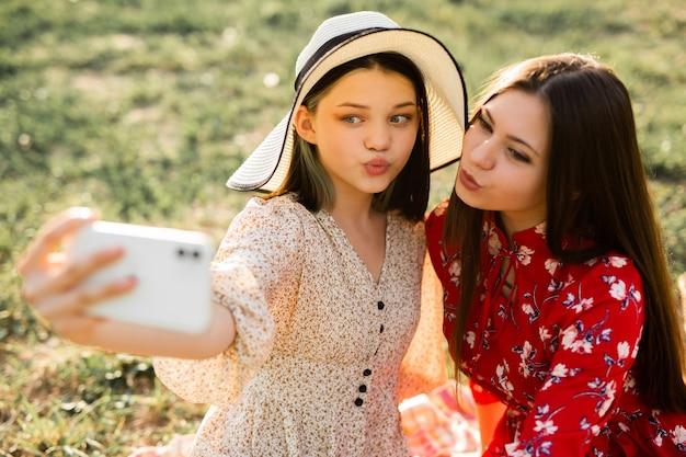 Selfie de duas belas jovens em um piquenique de verão