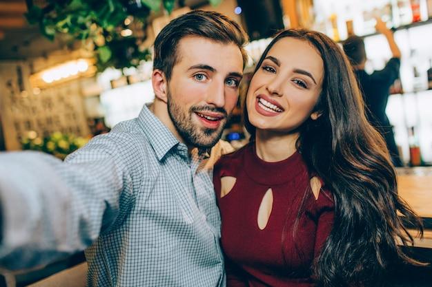 Selfie de duas pessoas bonitas, sentados juntos em um bar. ele está tirando uma foto deles enquanto ela está apenas sorrindo com um sorriso adorável.