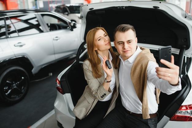 Selfie de família na concessionária. jovem casal feliz escolhe e compra um carro novo para a família.
