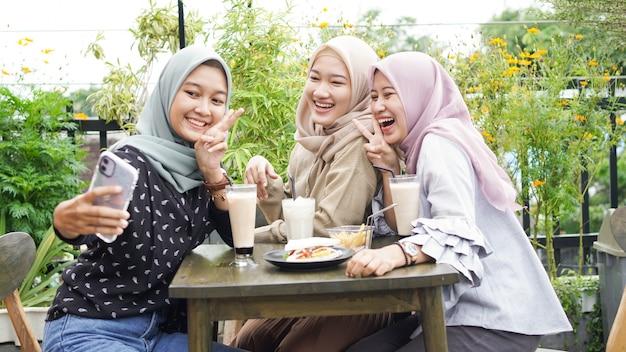 Selfie de grupo de mulher asiática com hijab em um café com uma amiga
