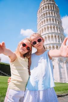 Selfie de meninas com a torre inclinada de pisa