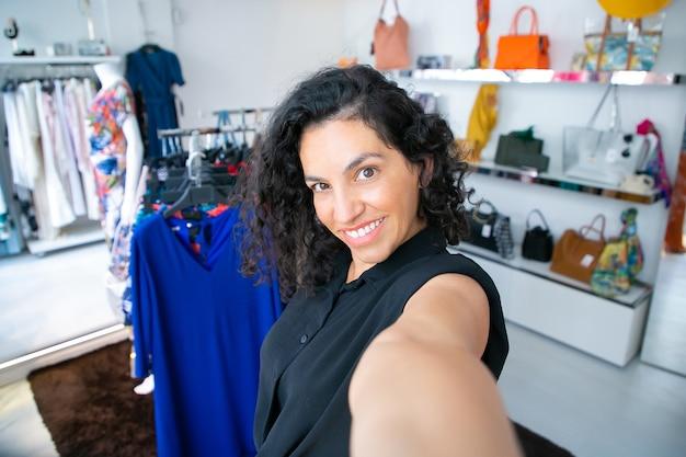 Selfie de mulher latina de cabelo preto feliz em pé perto da prateleira com vestidos na loja de moda, olhando para a câmera e sorrindo. cliente de boutique ou conceito de assistente de loja