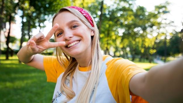 Selfie de mulher sorridente fazendo sinal de paz