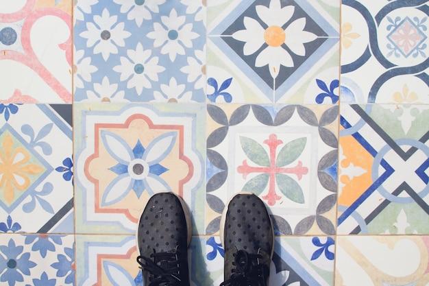 Selfie de pés com sapatilhas no piso de azulejos padrão de arte vintage, vista superior