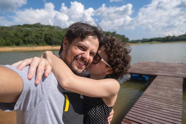 Selfie de um casal se abraçando na natureza.