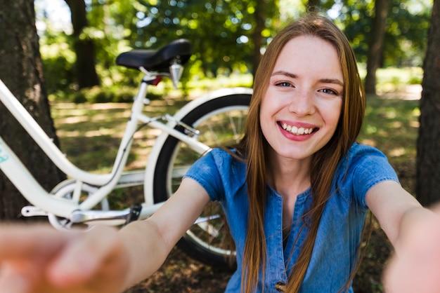Selfie de uma mulher sorridente ao lado de bicicleta