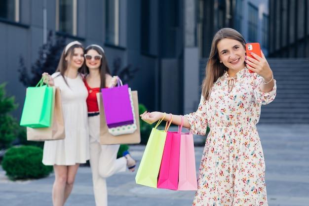 Selfie depois de fazer compras com sucesso. mulheres bonitas com sacolas de compras, fazendo selfie em pé na loja.