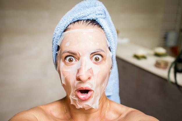 Selfie do divertimento de uma jovem mulher com máscara branca em sua cara e luz - toalha azul em sua cabeça.