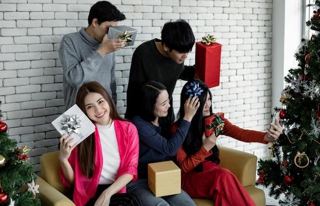 Selfie do grupo de jovens asiáticos com presentes em casa para comemorar o festival de natal. adolescentes tailandeses comemoram o natal e o ano novo. feliz natal e boas festas.