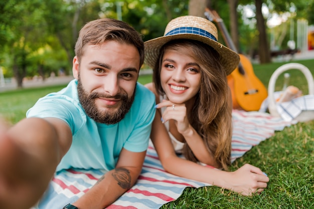 Selfie do jovem casal no piquenique no parque com guitarra e cesta de frutas
