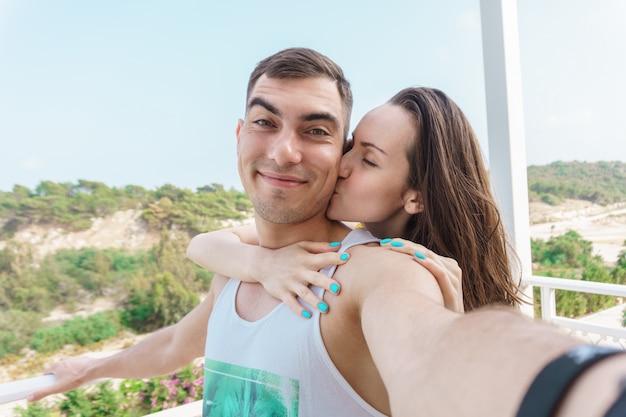 Selfie fofa de um jovem casal, uma mulher beijando a bochecha de um homem