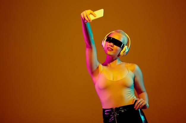 Selfie. jovem mulher caucasiana na parede marrom em luz de néon. linda modelo feminino com óculos elegantes e modernos. emoções humanas, expressão facial, vendas, conceito de anúncio. cultura do freak.