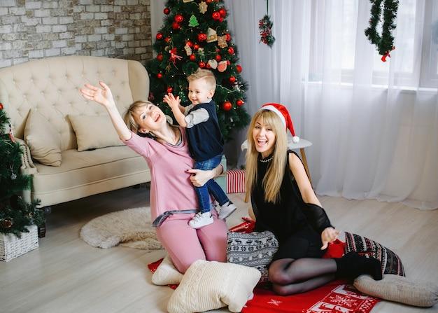 Selfie linda jovem mulher asiática com smartphone e celebração com o melhor amigo. rosto sorridente no quarto com decoração de árvore de natal para o festival de férias. conceito de festa e celebração de natal.