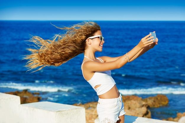 Selfie louro da foto da menina adolescente no smartphone na praia