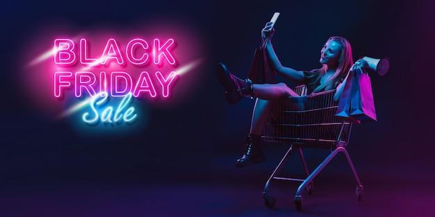 Selfie, megafone. retrato de jovem em néon no fundo escuro do estúdio. emoções humanas, sexta-feira negra, cyber segunda-feira, compras, vendas, conceito de finanças. copyspace. postagem perfeita para instagram.
