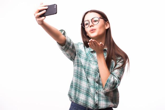 Selfie .. mulher jovem e atraente segurando um celular e tirando uma foto de si mesma em pé contra um branco